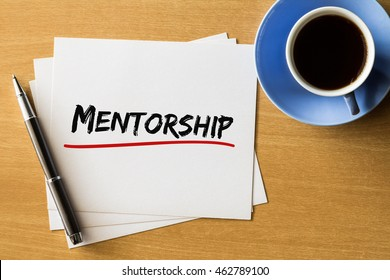 Mentorship - handwriting on papers with cup of coffee and pen, business concept
