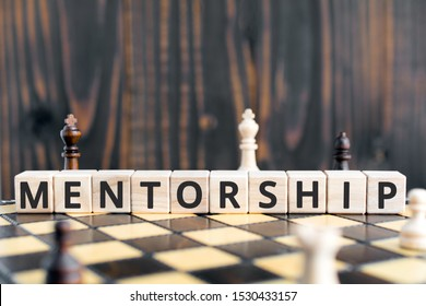 Mentorship - word from wooden blocks with letters, mentoring  mentorship concept, random letters around, white  background