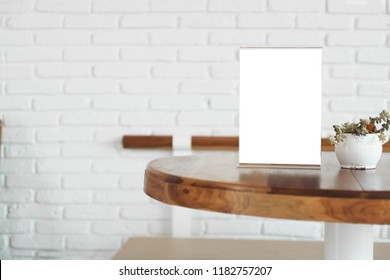 Menu Card Holder with white sheet of paper on table in cafe.Card display Promotion and Information for customer,Picture stand,Sign Holder and Photo Frame Mock up template.