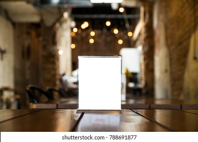 Menu Card Holder with white sheet of paper on table in cafe.Card display Promotion and Information for customer,Picture stand,Sign Holder and Photo Frame template.
