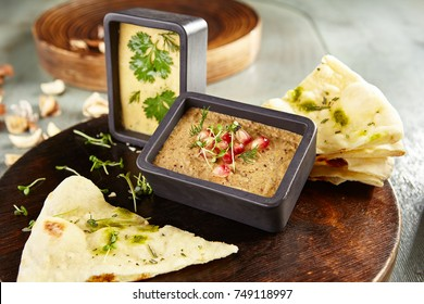 Menu of gastronomic restaurant. Cold appetizer - hummus of chick pea and eggplant pate with fresh herbs and pomegranate seeds on wooden round board