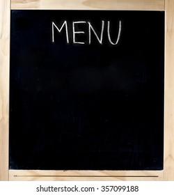 Menu handwritten with white chalk on blackboard in wood frame isolated