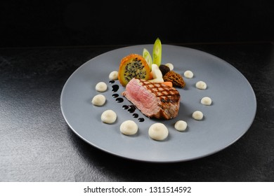 menu main course with roasted veal, morels and vegetables on a blue gray plate on a dark table, copy space, selected focus, narrow depth of field