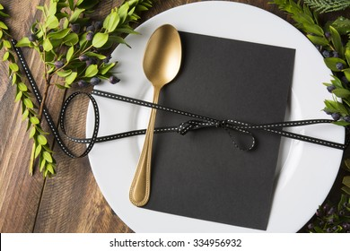 menu place setting with empty card and golden spoon over wooden background, surrounded by green branches
