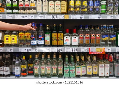 MEPPEN, GERMANY - AUGUST 21, 2018: Shelves with a selection of liquors. Display of various German grain brandy in a REWE supermarket.