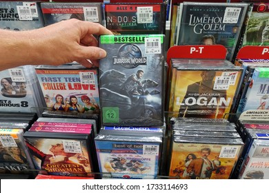 MEPPEN, GERMANY - AUGUST 21, 2018: DVD movie: Jurassic World. Shopper selecting a dvd in a media aisle of a shop. Jurassic World is a 2015 American science fiction adventure film.