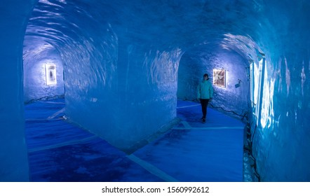 MER DE GLACE GLACIER, FRANCE, MAY 2018: Female tourist walks through the breathtaking blue lit gallery inside an ice cave. Young Caucasian woman explores the icy corridors inside Mer De Glace glacier.