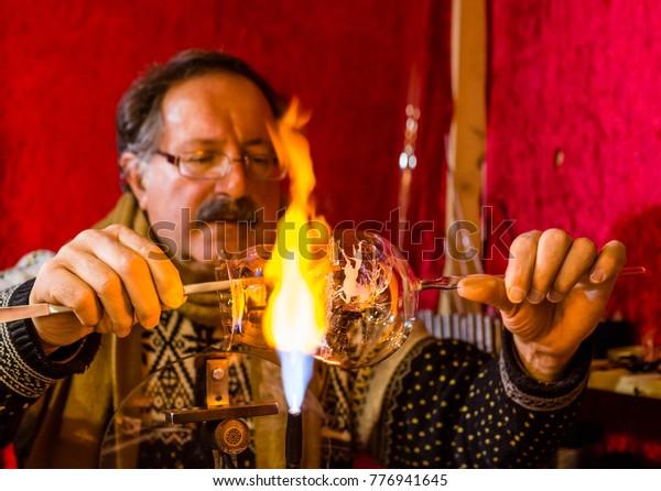 Meran, South Tyrol, Italy - December 16, 2017: A man is making glass Christmas balls at the Meran Christmas Market (Merano)