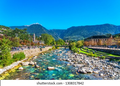 MERAN, SOUTH TYROL / ITALY - SEPTEMBER 28, 2018: Passer river view in Meran spa town and riverside plenty of tourists. On the right a view of the Therme Meran.
