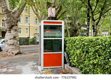 MERANO, ITALY - SEPTEMBER 2 : Public telephone on pathway beside traffic road in small alley for people to use at Meran or Merano city on September 2, 2017 in South Tyrol, Italy
