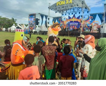Merauke, Papua, Indonesia - September 25, 2021 : children are still scrambling to shake hands or take pictures with the mascot of PON XX Papua 2021