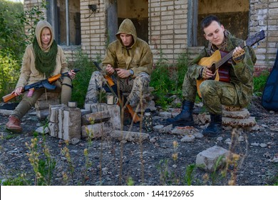 Mercenaries or soldiers of fortune (two mans and one woman in military clothes) with machine guns, rifles and a guitar rest in camp near the fireplace