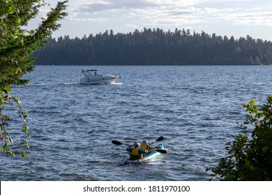 MERCER ISLAND, WASHINGTON/USA - Sep 7, 2020: Motor sport and kayaking on Lake Washington on a sunny summer day with lots of clouds in the sky.