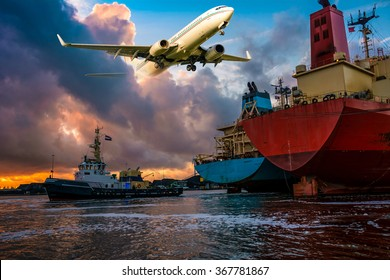 Merchant cargo ships assist by a tugboat are busy with mooring operations during sunset in port. Airplane is flying through the colorful clouds. Nice Industrial oil tanker/aviation background.