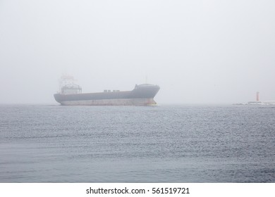 The merchant, commercial ship moves down the river in foggy, winter day