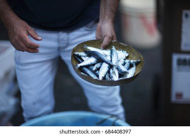 A merchant in the fish market holds fish in a pan of weights