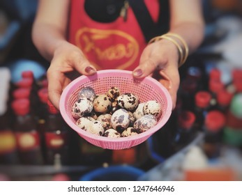 The merchant holding hands small quail eggs in the local market. The eggs in hand of seller.