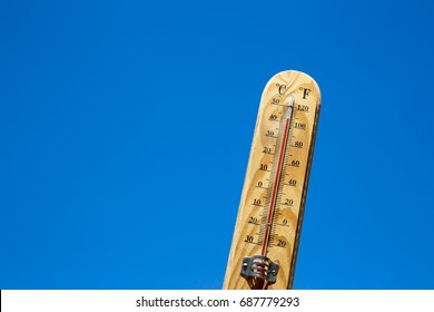 Mercury thermometer marking 42 degrees Celsius 108 Fahrenheit in a sunny day. Summer heat shown on mercury thermometer against the blue sky.