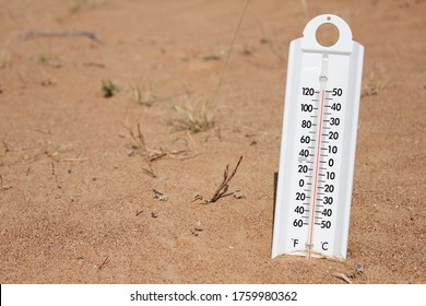 Mercury thermometer shows very hot summer temperature on both fahrenheit and celsius scale in dry desert sand dunes in the Middle East. Climate change/global warming/desert concept.