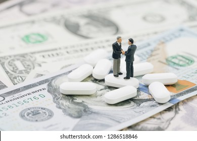 Merger or business discussion for health care and medical industry concept, miniature businessman shaking hand standing on white tablet pills on US dollar banknotes, success in medical research deal.