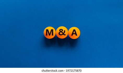 Mergers and acquisitions symbol. Concept word 'M and A, Mergers and acquisitions' on orange table tennis balls on a beautiful blue background. Business, mergers and acquisitions concept. Copy space.