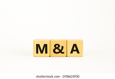 Mergers and acquisitions symbol. Concept words 'M and A - Mergers and acquisitions' on wooden cubes on a beautiful white background. Business, mergers and acquisitions concept. Copy space.