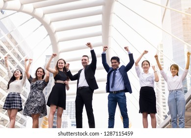 Mergers and acquisition,Successful group of business diversity people,Team success achievement hand raised up over blurred building