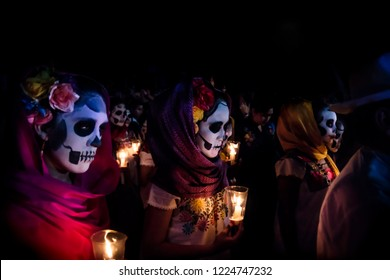 Merida, Cementerio General, Mexico - 31 October 2018: Three women with Catrina customes, scarves on their head and flowers in the hair with skull make-up holding candels surrounded by costumed people