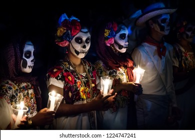 Merida, Cementerio General, Mexico - 31 October 2018: Three women with Catrina customes and man with white cowboy dress with skull make-up holding candels at the parade for dia de los muertos at the