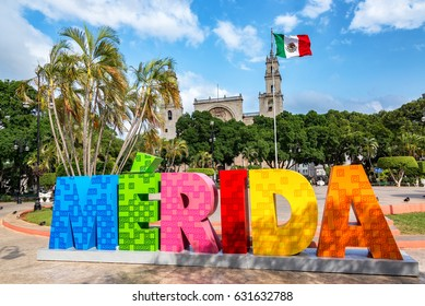 MERIDA, MEXICO - FEBRUARY 21: Colorful Merida sign with a Mexican flag and cathedral in the background in Merida, Mexico on February 21, 2017