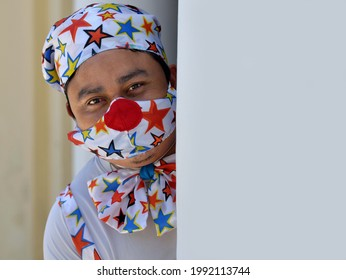 MERIDA, YUCATAN, MEXICO - APRIL 25, 2021: Male clown in clown outfit and colorful face mask peeks around corner during global coronavirus pandemic, on April 25, 2021.