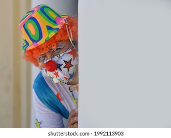 MERIDA, YUCATAN, MEXICO - APRIL 25, 2021: Male clown with orange wig, in clown outfit and colorful cloth face mask peeks around a corner during the global coronavirus pandemic, on April 25, 2021.