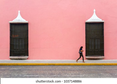 Merida, Yucatan / Mexico - Circa 2016: A woman walks alonne on a sidewalk while she checks her cell phone. This city is one of the safest city in the country.