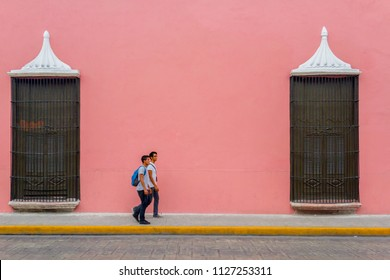 Merida, Yucatan / Mexico - Circa 2017: Two young men walk  along a sidewalk with a beautiful pink facade of a house. This city is one of the most famous in the country due to its colonial style.
