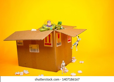 MERIDA, YUCATAN/MEXICO- July 2015: A humorous scene of toys (Starwars and toy story characters) unboxing a  package box isolated in yellow background. Buzzlightyear, rex, clonetrooper, stormtrooper