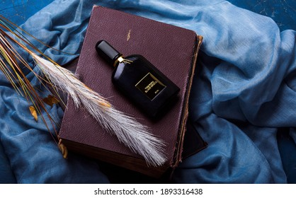 MERIDA-YUCATAN-MEXICO-DECEMBER-2020: Black Orchid perfume in a black glass bottle by the famous designer Tom Ford, which is located on a brown book and wheat stick and with a blue cloth background.