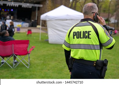 Meriden, CT USA. Apr 2019. Daffodil Festival. Police officer on phone vigilant around the festival grounds.