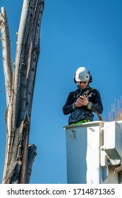 Meridian, Idaho, USA – April 8, 2020: Tree cutter stops what he was doing to send a text
