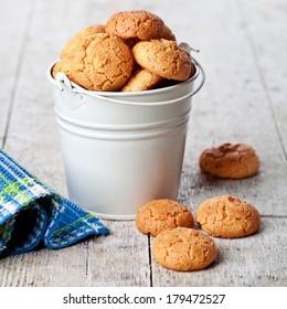 meringue almond cookies in bucket on wooden background