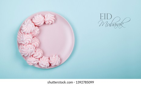 Meringue arranged in the shape of crescent moon with the text Eid Mubarak which is islamic greeting in the occasion of Eid festival