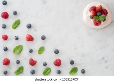 Meringue Beside a Pattern of Blueberries, Raspberries and Mint on Marble Table top with Copy Space From Above