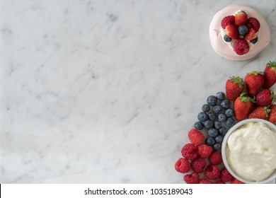 Meringue Beside a Selection of Raspberries, Strawberries, Blueberries and Cream on Marble Table Top from Above with Copy Space