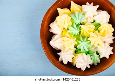 Meringue in a bowl on a blue  wooden background, top view. Delicious dessert. Colorful handmade meringue.