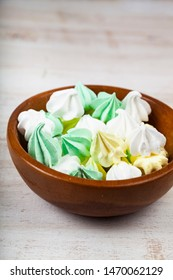 Meringue in a bowl on a wooden background. Delicious dessert. Colorful handmade meringue.