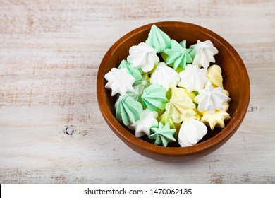 Meringue in a bowl on a wooden background, top view. Delicious dessert. Colorful handmade meringue.