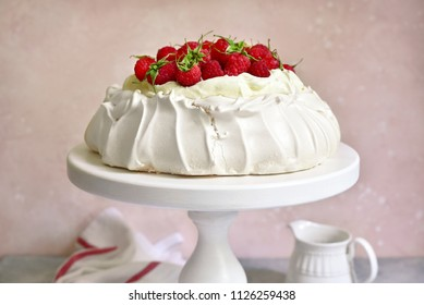 "Meringue cake ""Pavlova"" with fresh ripe raspberry and whipped cream on a light slate, stone or concrete background."