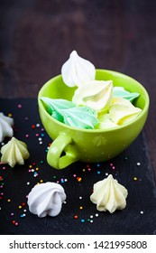 Meringue in a green cup on a dark background. Delicious dessert. Colorful handmade meringue.