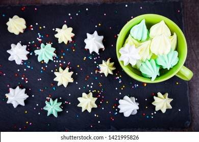 Meringue in a green cup on a dark background, top view. Delicious dessert. Colorful handmade meringue.
