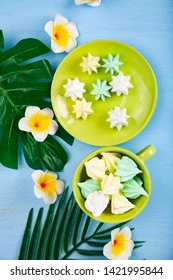Meringue in a green cup with tropical leaves and flowers. Delicious dessert. Colorful handmade meringue.