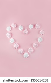 Meringue heart on pink background.